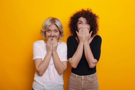 Caucasian curly haired brunette is feeling surprised near her blonde sister covering their mouths with hands on a yellow background