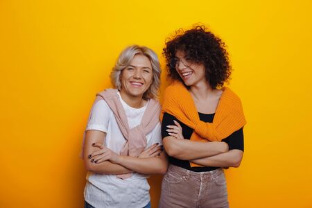 Two nice caucasian woman with curly hair are posing confidently with crossed hands on a yellow background while smiling and having fun Reklamní fotografie
