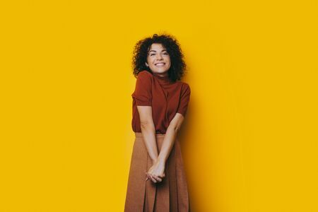Lovely caucasian girl with curly hair and cheerful smile posing in a nice dress with crossed hands on a yellow background