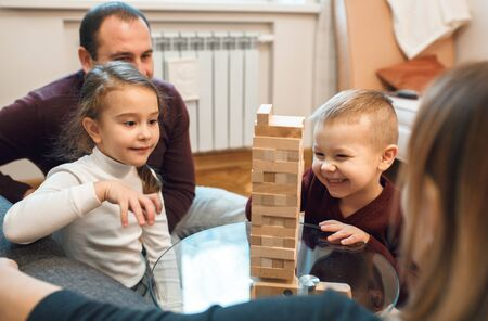 Smiling caucasian boy is playing blocks with his bigger sister while their parents are looking proudly