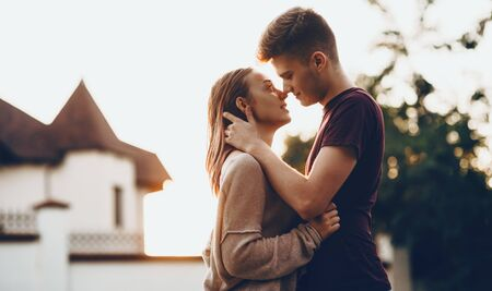 Caucasian couple kissing each other in front of the sunset embracing and having great moments together