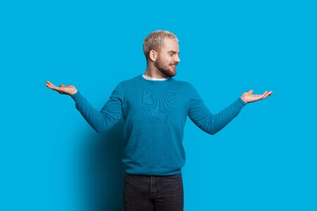 Caucasian man with blonde hair and beard is gesturing a balance with his hands looking and smiling cheerfully on a blue wall
