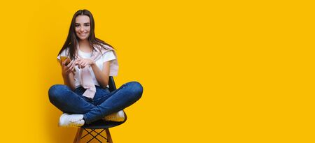 Charming caucasian girl sitting on a chair and using a phone while posing near yellow freespace Stock Photo