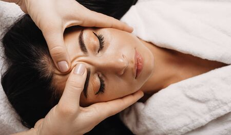 Caucasian girl with black hair who is sleeping during a facial massage at spa