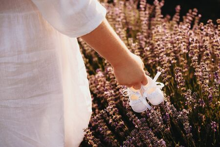 Plump mother holding a pair of baby shoes and walking in a lavender field while wearing a nice white dress