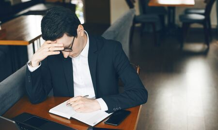 Thinking caucasian businessman is trying to write something while waiting a phone call