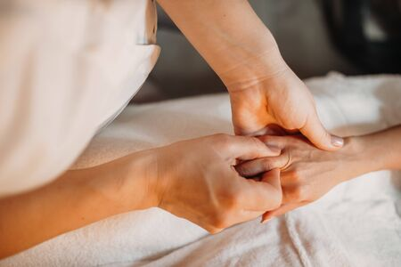 Young masseur is massaging woman's fingers to make them relaxed after spa sessions