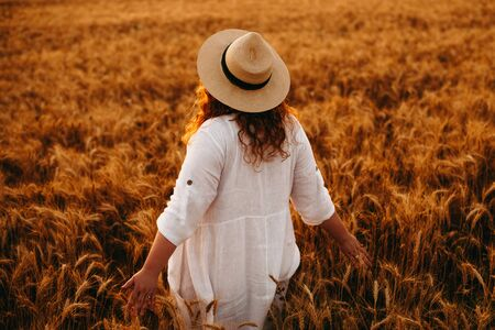 Plump caucasian lady dressed in a white dress and wearing a hat is posing in wheat field