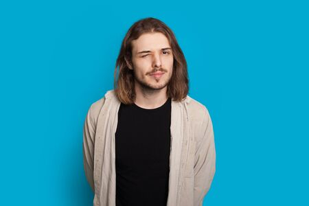 Bearded caucasian man with long hair is blinking while posing on a blue background Stock fotó
