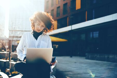 Concentrated caucasian woman with curly hair is working with her computer outside while wearing eyeglasses and holding her phone