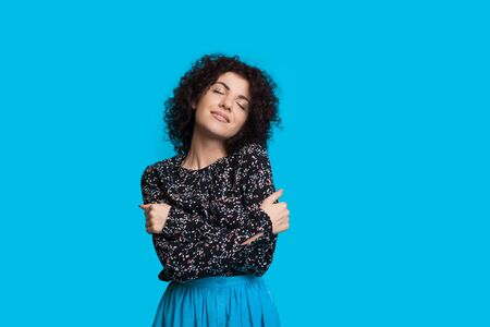 Curly haired caucasian woman embracing herself while posing on a blue background Stock Photo