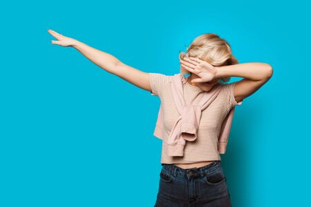 Nice blonde haired caucasian lady dabbing cheerfully on a blue background