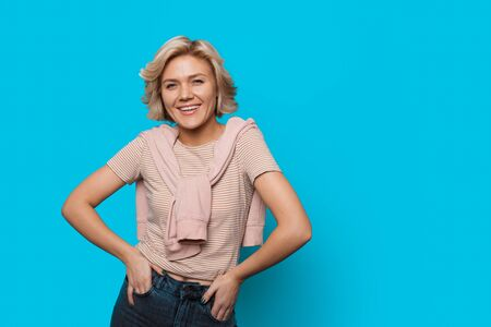Charming caucasian lady with blonde hair is holding her hands in the pockets while smiling on blue wall with free space