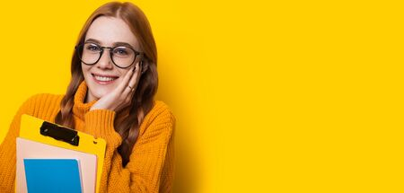 Close up portrait of a caucasian student with red hair and freckles holding some books and posing on a yellow wall with blank space