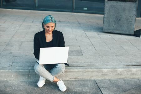 Charming caucasian freelancer with blue hair is sitting in the street and working at her computer Zdjęcie Seryjne