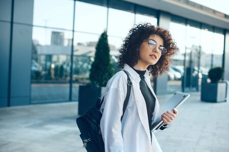 Serious caucasian student with glasses and curly hair is posing while holding a laptop and a bag