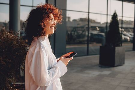 Cheerful caucasian woman with curly hair and eyeglasses is chatting with somebody while looking away