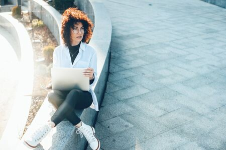 Concentrated caucasian entrepreneur sitting outside while working at the computer