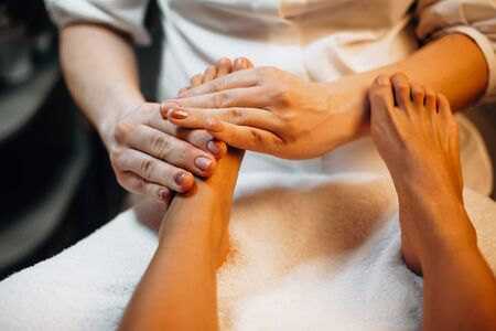 Careful spa worker is massaging clients feet before moving to the next spa procedure