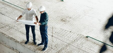 Upper view portrait of two engineers looking at the buildings plan while holding a map