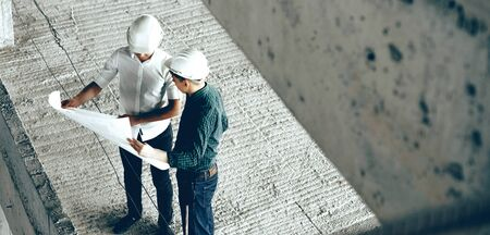 Two adult professional constructors discussing the future building plan while holding a big sheet of paper