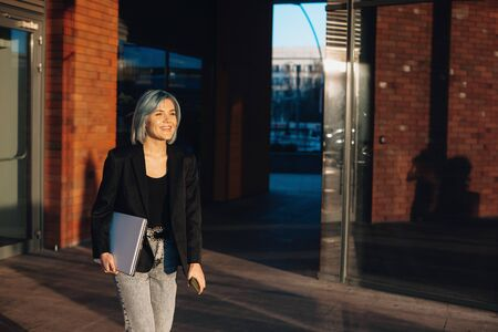 Caucasian woman with blue hair walking outside with a computer and smiling cheerfully