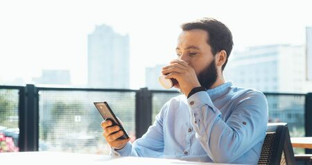 Busy caucasian man with beard chatting on phone while drinking a cup of coffee at the cafeteria