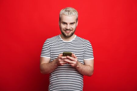 Blonde caucasian man chatting with his friends on a red background while looking at camera