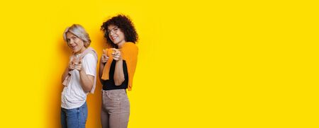 Caucasian women with curly hair are pointing at camera cheerfully while posing on a yellow free space background Standard-Bild