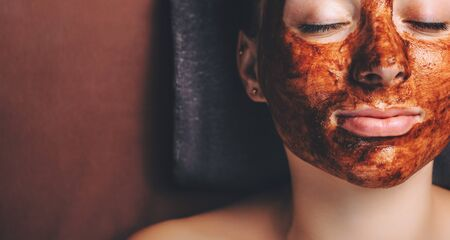 Chocolate mask applied on the womans face while she is lying with closed eyes near free space