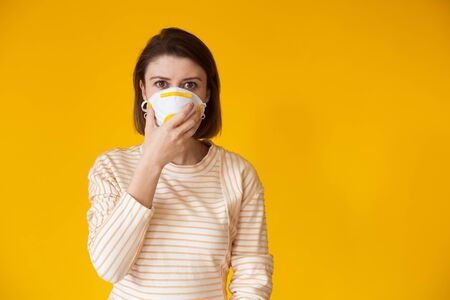 Caucasian lady posing on a yellow background with free space while wearing a mask with filter