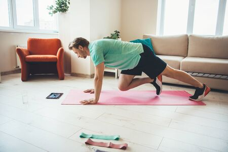 Caucasian man doing sport exercises at home while looking at the tablet on the floor