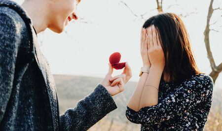Surprised caucasian girl asked to get married by her lover in a field is covering her face with palms in front of the wedding ring