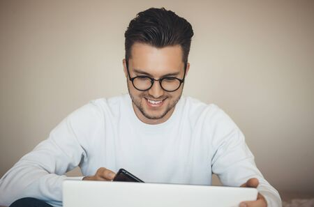 Happy young caucasian man with eyeglasses is buying something online during the lockdown using the laptop and mobile Stock Photo