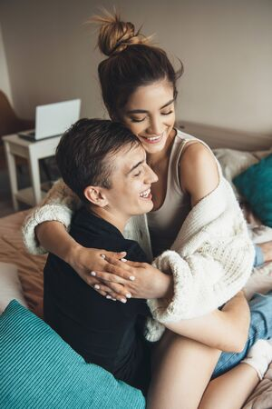 Caucasian girl with brown hair embracing her lover in the bed and smile