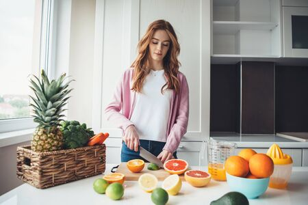 Ginger lady with freckles slicing fruits before squeezing the for juice Stockfoto