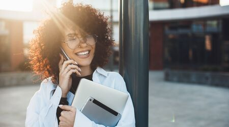 Curly haired caucasian businessperson having a phone discussion while posing with a laptop in the light of the sun outside Stock Photo