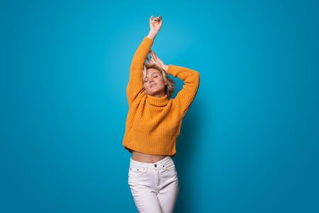 Delightful caucasian blonde woman in yellow sweater is posing with hand above on blue studio wall