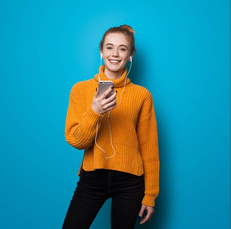 Caucasian ginger woman with freckles smiling at camera while listening to music and holding a phone on blue studio wall