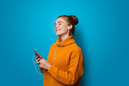 Cheering caucasian lady with freckles and red hair smiling while listening to music on a blue wall