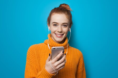 Lovely ginger woman with freckles smiling at camera in a orange sweater on a blue studio wall listening to music through earphones