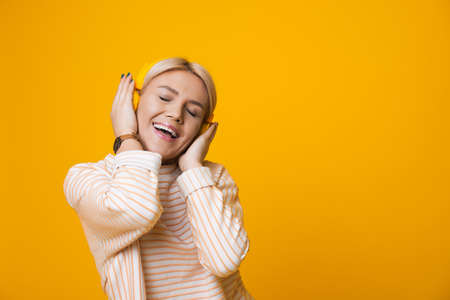 Monochrome photo of a caucasian woman listening to musing from headphones on a yellow wall with free space