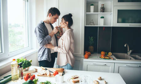 Lovely young couple drinking together mojito while preparing dinner together in the kitchen Archivio Fotografico