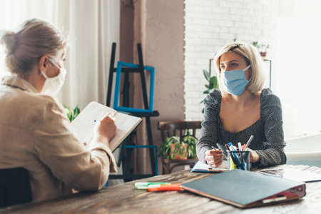 Busy senior businesswoman working from home with a client wearing a medical mask on face and using some book and documents Фото со стока