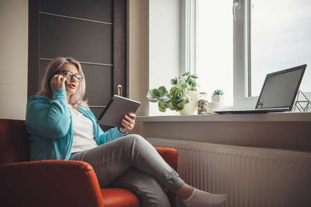 Busy senior woman with blonde hair and eyeglasses holding a tablet and talking on phone while working from home Banco de Imagens