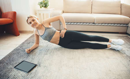 Sporty caucasian woman in sportswear is side planking on the floor smiling at camera and using a tablet