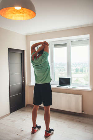 back view photo of a caucasian man doing fitness at home using a laptop near the window