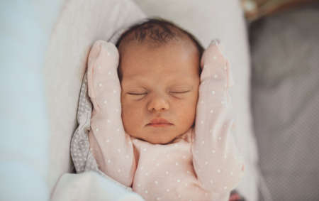 Close up photo of a newborn baby sleeping in white clothes at home