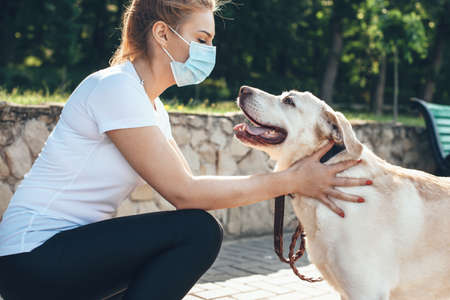 Young blonde woman touching her dog while wear medical mask on face and walk in park