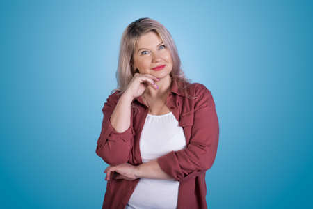 Caucasian woman posing on a blue studio wall gesturing a wonder touching her chin and look at camera